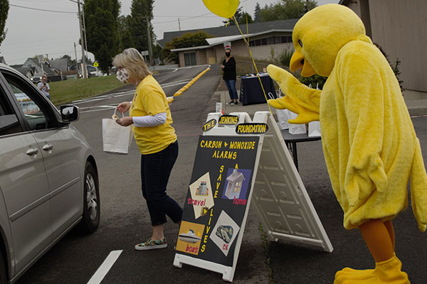 bird mascot costume handing out carbon monoxide alarms