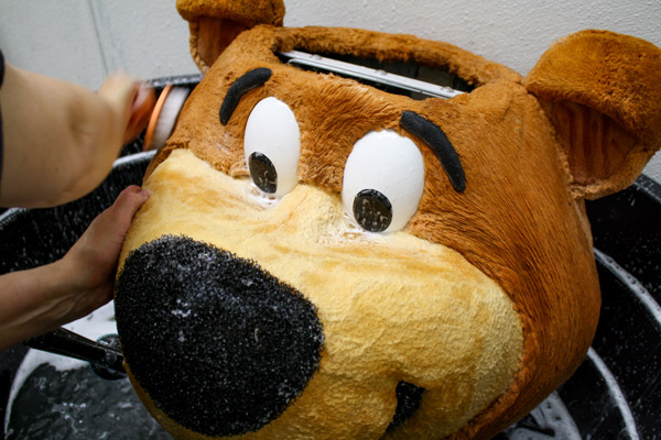 Yogi bear mascot head being hand washed with soap
