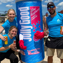 Dark blurred background photo of happy athletes with a beverage mascot