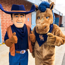 Cowboy and horse mascot pose together