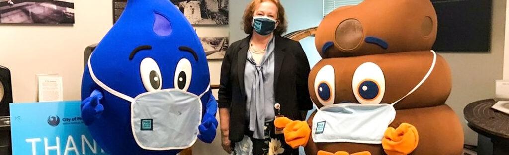 Wayne the Rain drop and Loo Poo wearing masks with woman
