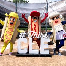 Cleveland Indian's hot dog mascots pose around sign