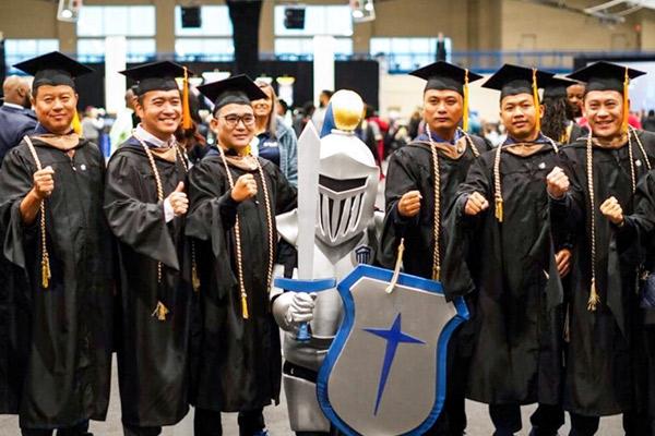 Sir Maximous posing with graduates