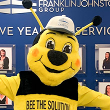 Smiling bee mascot posing in front of employee picture wall