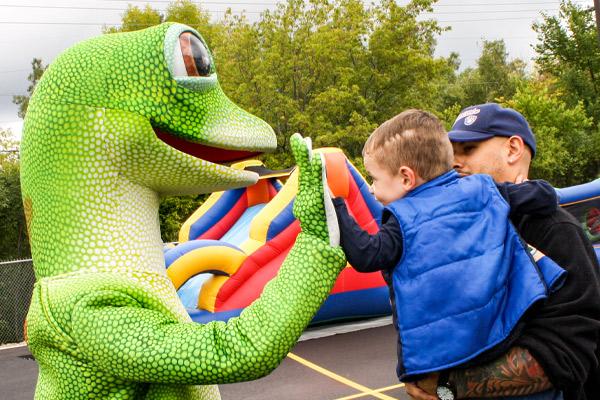 Gieco Gecko high-fives a little kid